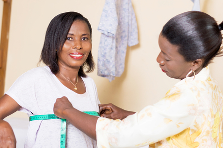 the seamstress takes the tower measuring the chest of her client. Banque d'images - 98428955