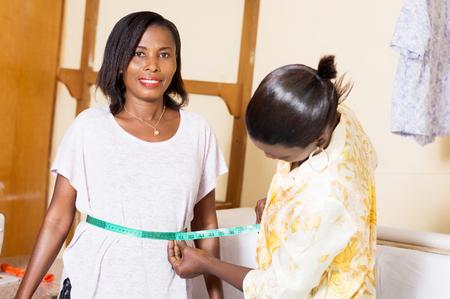 Jeune couturière prend la mesure de la taille de son client Banque d'images - 98428958