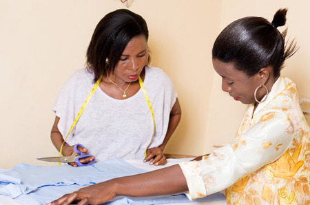 the teacher in sewing shows his student how to take measures for cutting. Banque d'images - 99014607
