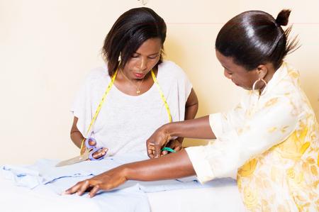 Le professeur dans la couture montre son étudiant comment faire mesure à couper Banque d'images - 99119702
