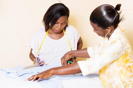 the teacher in sewing shows his student how to take measures for cutting. Banque d'images - 99119702