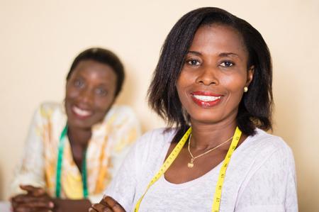 Couturière souriante dans son atelier regarde la caméra avec son collègue dans le fond . Banque d'images - 100022827