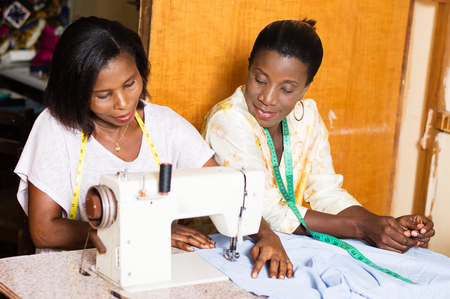 the student is happy to learn sewing and pleases her teacher. Banque d'images - 100028098