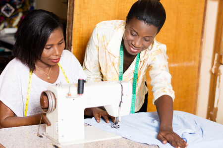 seamstress teaches her students how to put a shirt under the needle of a sewing machine. Banque d'images - 100056346