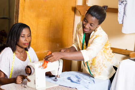 Sewing teacher shows her student how to place a roll of yarn on a sewing machine Banque d'images - 101106138