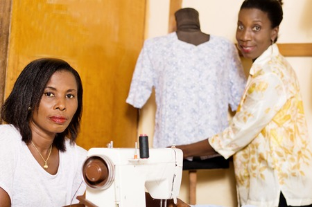 Young seamstress in front of her sewing machine while her colleague dresses the mannequin Banque d'images - 100118552