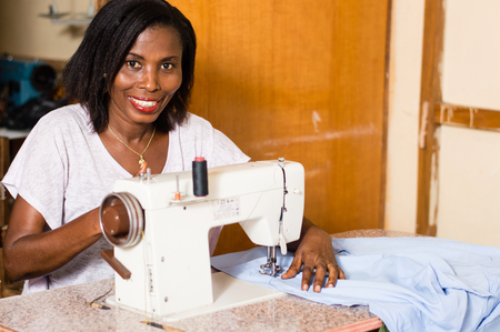 Young African woman smiling sewing in her studio in the quiet. Banque d'images - 100118555