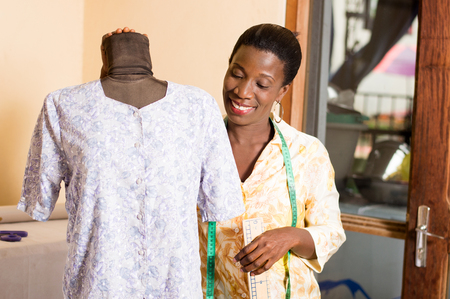 Young seamstress smiling satisfied with her work, admires her mannequin. Banque d'images - 100077055