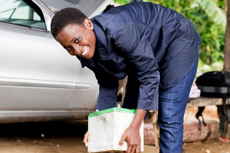 Young woman mechanic lifting a car battery in her workshop. Banque d'images - 102144178