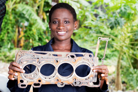 Young woman mechanic holds a damaged car part in her workshop. Banque d'images - 102003250