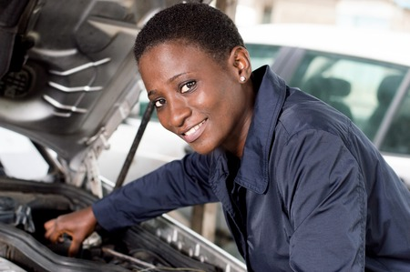 Young female mechanic repairs a car by putting the engine in good condition. Banque d'images - 102189396