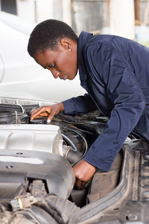 Young female mechanic repairs a car by putting the engine in good condition. Banque d'images - 102144179