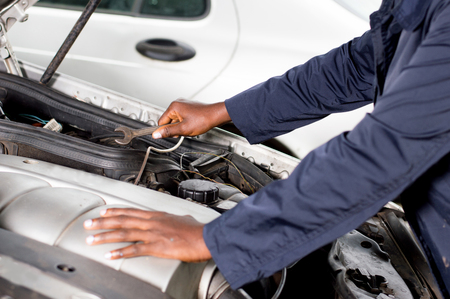 Closeup of a hand holding a key on the engine of a broken car. Banque d'images - 103375121
