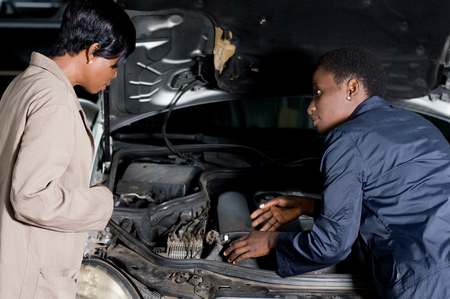 The mechanic explains the breakdown of the car at its owner at the workshop. Banque d'images - 102912573