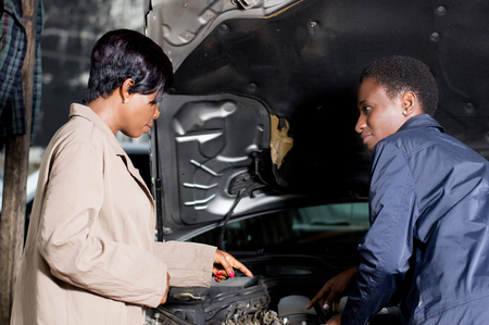 The mechanic explains the breakdown of the car at its owner at the workshop. Banque d'images - 102909752