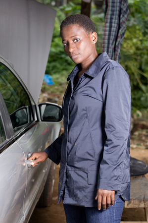 Young mechanic opening the door of a car in the garage and looking at the camera Banque d'images - 102912574