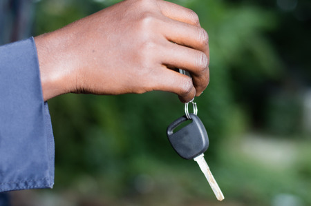 A hand holding a car ignition key outside. Banque d'images - 102877878