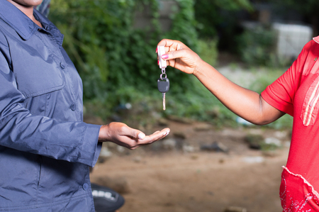 Young woman in red gives the key of her car to the mechanic in a garage. Banque d'images - 102889712