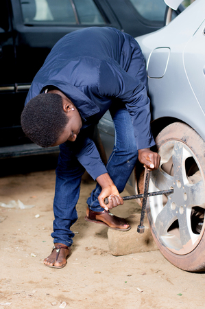 Young mechanic removing the wheel of a car in a workshop. Banque d'images - 102877879