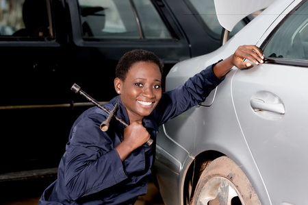 Young smiling mechanic squatting at the door of a car she is preparing to remove. Banque d'images - 102941829
