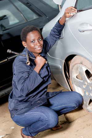 Young smiling mechanic squatting at the door of a car she is preparing to remove. Banque d'images - 102889453