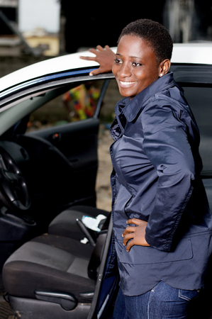 Young female mechanic standing beside this car is happy to settle the breakdown. Banque d'images - 102941831