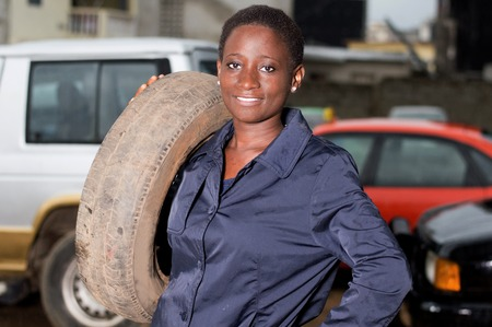 Young mechanic standing and smiling has a tire on her shoulder in her studio. Banque d'images - 111828755