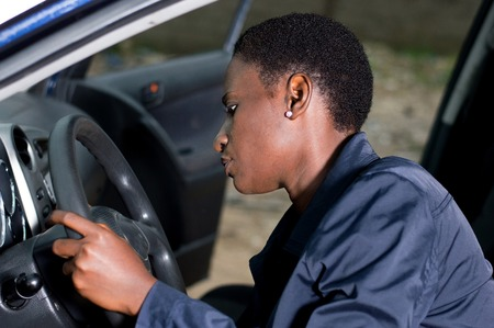 A young mechanic sitting at the wheel of a car, checks her ignition. Banque d'images - 111828758
