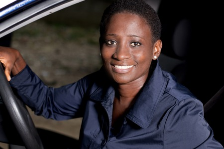 Young woman sitting in a car, hands on the steering wheel smiling at the camera. Banque d'images - 111828759