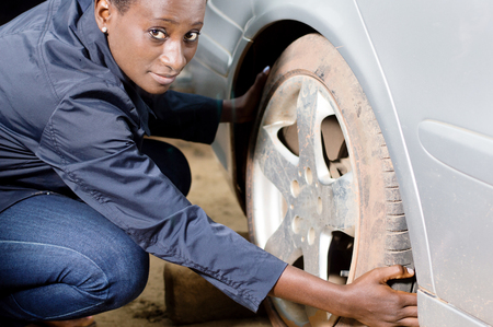 Young woman mechanic squatting near a car removes her tire. Banque d'images - 111828762