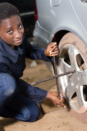Young woman mechanic on her knee, removes the tire from a car she wants to replace. Banque d'images - 111828763