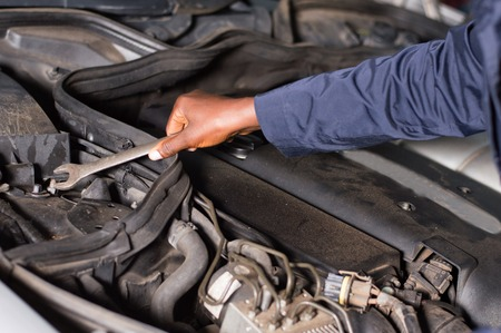 Close-up of a hand holding a key on the engine of a broken car. Banque d'images - 111828768