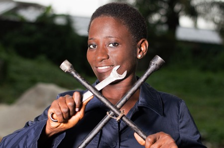 Young smiling mechanic showing her tools in her outdoor studio. Banque d'images - 111828769