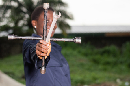Young smiling mechanic showing her tools in her outdoor studio. Banque d'images - 111828770