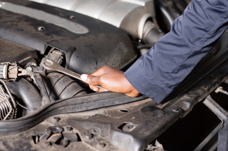 Closeup  of a hand holding a key on the engine of a broken car. Banque d'images - 111828771