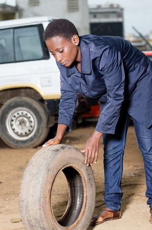 Young female mechanic holds a backup tire for spare in a car workshop. Banque d'images - 111828779