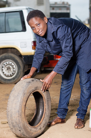 Young female mechanic holds a backup tire for spare in a car workshop. Banque d'images - 111828780