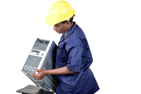 Young female computer repairer checks a central unit by lifting it. Banque d'images - 111828802