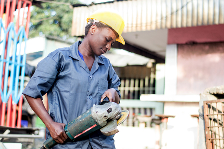 Young woman holding her working tool and ready to polish a welded iron. Banque d'images - 111828843