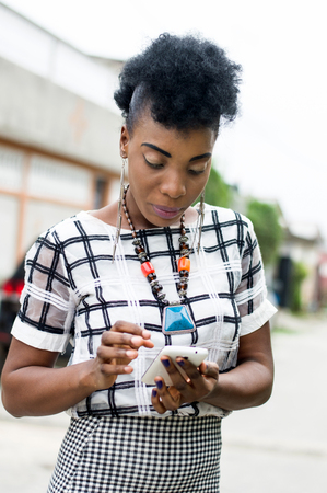 Portrait of African woman focused on her mobile phone. Banque d'images - 119444213