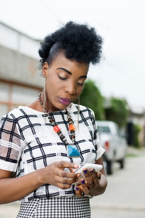 Portrait of African woman focused on her mobile phone. Banque d'images - 119444214