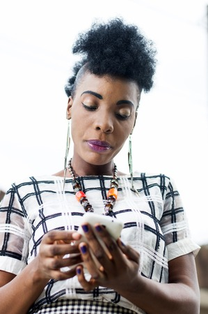 Portrait of African woman focused on her mobile phone. Banque d'images - 119444216