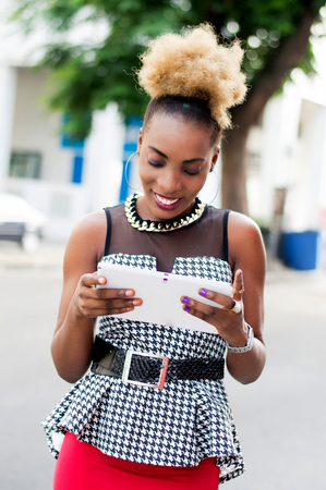 Young businesswoman standing by the roadside smiles as she looks at her tablet. Banque d'images - 119444240