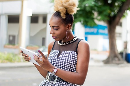 Young businesswoman consulting her tablet standing by the roadside. Banque d'images - 119444244