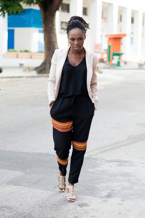 Pretty African woman hands in pockets crosses the road looking at the camera. Banque d'images - 119444250
