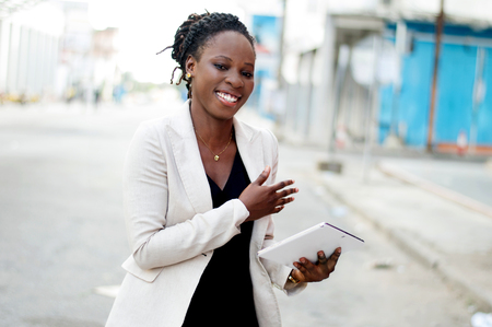 Young businesswoman smiling holding a computer tablet in the street. Banque d'images - 119444253