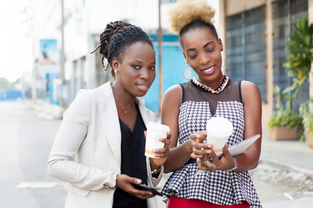 Smiling young businesswomen sharing boxes of milk and a tablet outside. Banque d'images - 119444255