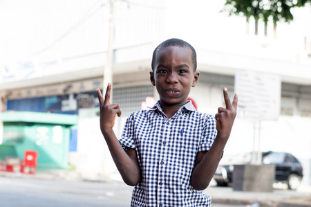 Happy little boy standing out by making signs of victory. Banque d'images - 119444258