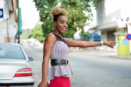 Pretty woman standing by the roadside, stopping a car with a sign Banque d'images - 119444083