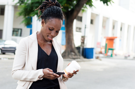 Young businesswoman sends messages with her cell phone. Banque d'images - 119444096